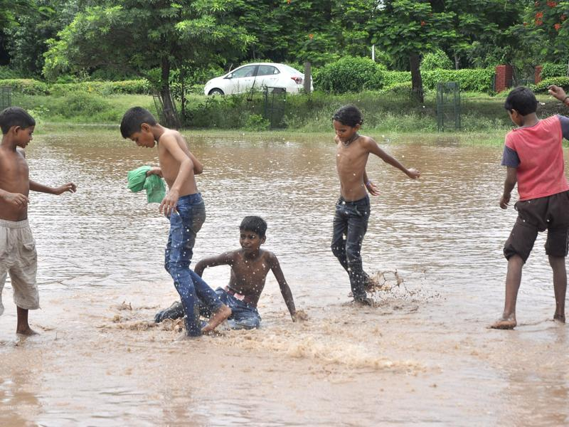 Children playing on a waterlogged street in Panchula on Saturday.  (Sant Arora/HT Photo)