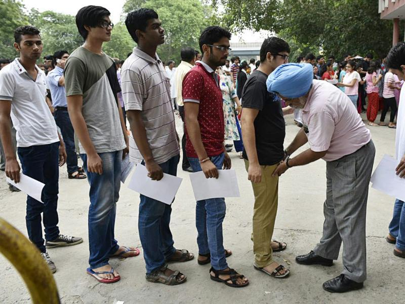 Candidates being frisked at Guru Harkrishan Public School, Vasant Vihar in New Delhi on Sunday. (Arvind Yadav / Hindustan Times)