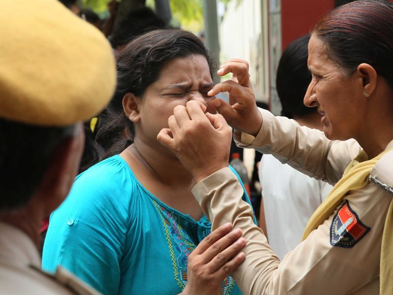 An aspirant of NEET-2 writhes in pain as a police woman assists her in removing her nose pin, an item not allowed inside the examination centre in Jaipur, Rajasthan on Sunday. (Himanshu Vyas/ Hindustan Times)