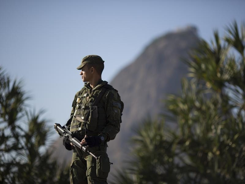 With Sugar Loaf mountain in the background a soldier patrols near Botafogo beach in Rio de Janeiro, Brazil. (AP Photo)
