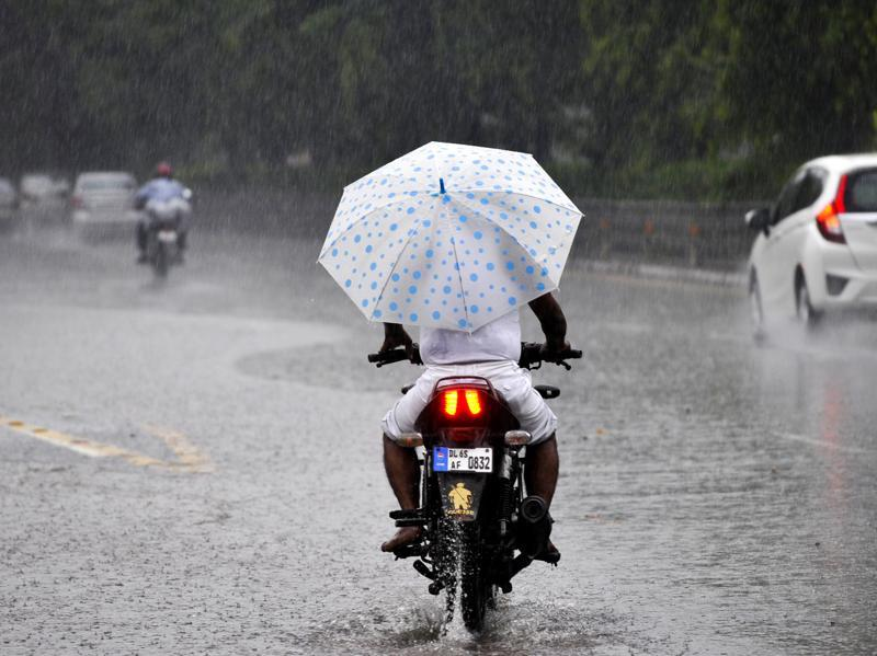 A man drives a motocycle as rains lashed across Noida. (Sunil Ghosh /HT Photo)