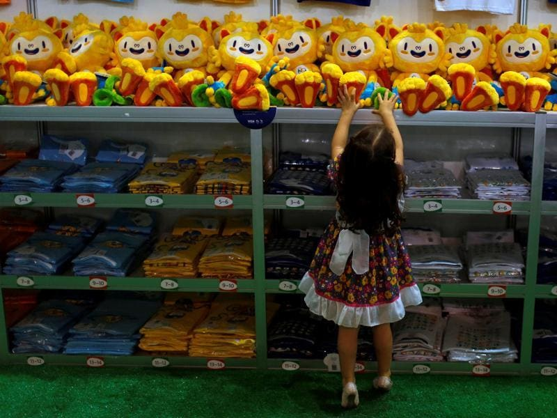 A child tries to reach a Rio 2016 Olympic mascot Vinicius doll during the opening of the Olympics megastore on Copacabana beach in Rio de Janeiro. (REUTERS photo)