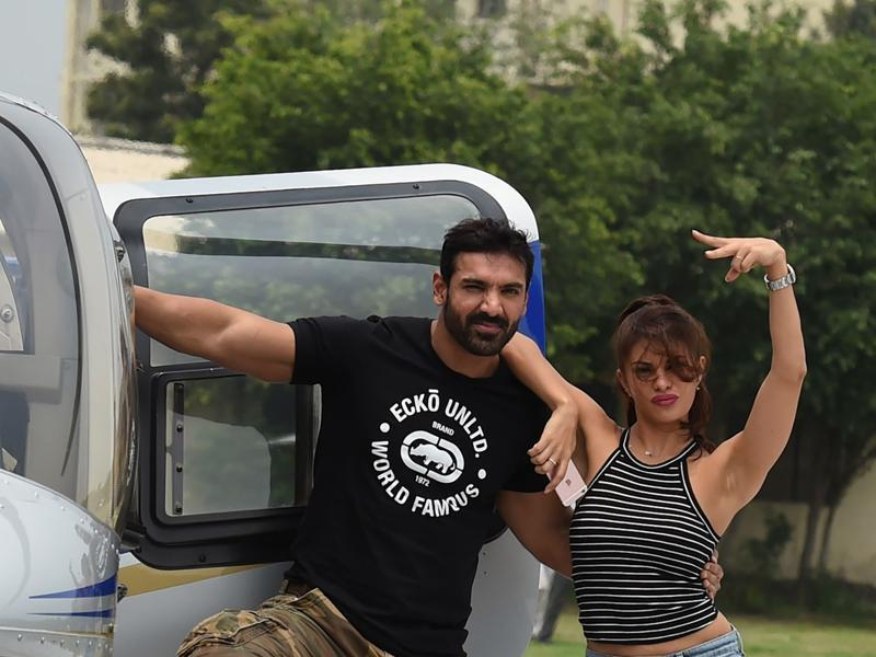 John Abraham and Jacqueline Fernandez pose with the helicopter during a promotional event of their Dishoom. (AFP)