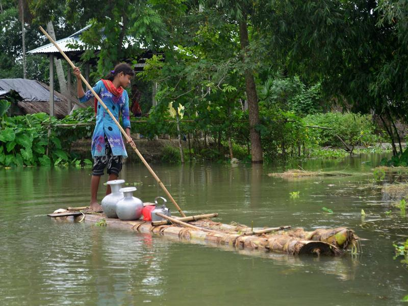 A girl pushes a banana raft in search of drinking water at Alikakh village in South Kamrup district of Assam on Monday.  (PTI Photo)