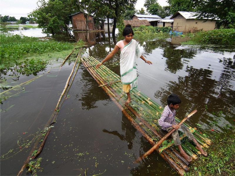 Villagers prepare to cross floodwaters on a banana raft in a village in Kaziranga national park. (PTI Photo)