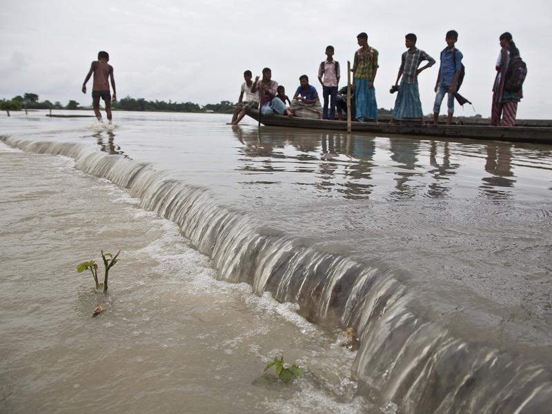Villagers on a boat move through a submerged road after heavy monsoon rains flooded Gagalmari village. (AP Photo)