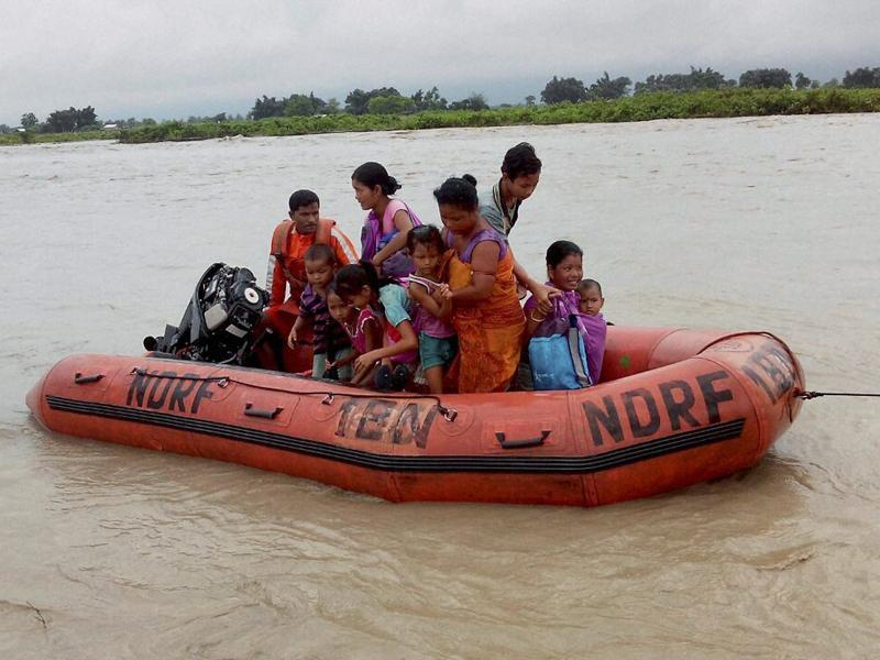 Disaster Response Force(NDRF) jawans rescue flood affected villagers , at Chirang district in Assam on Tuesday.  (PTI Photo)