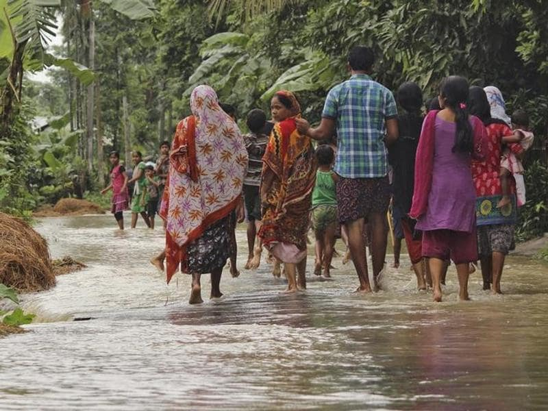 A woman (C) looks on as she walks with others to a safer place through a flooded road after incessant rains at Bullut village in Kamrup district in Assam. (Reuters)