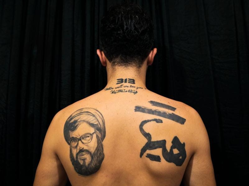 Hamza, 25, poses for a photo showing off his tattoos of Hezbollah leader Hassan Nasrallah and Shiite Muslim slogans. The tattoo in Arabic reads: It is impossible to humiliate us. (AP)