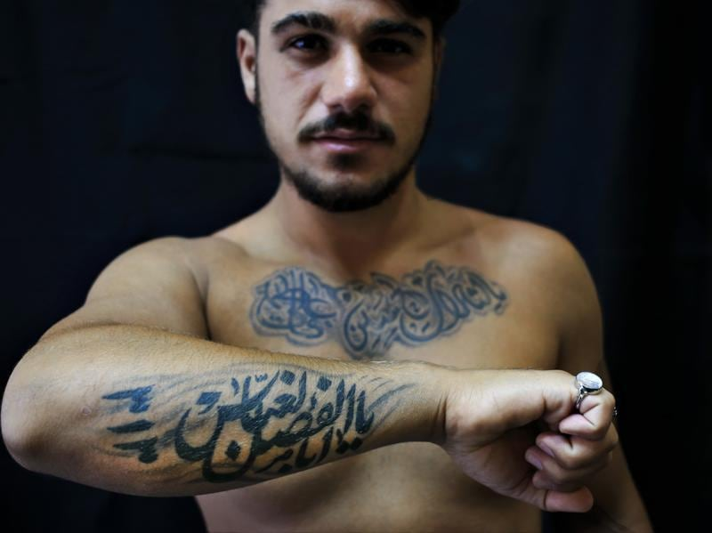 Alodi Issa, 22, poses for a photo showing off his tattoos with Shiite Muslim religious slogans in the southern suburb of Beirut, Lebanon on July 18, 2016 photo. The tattoo in Arabic reads: Oh, the revenge for Hussein. Ali, Fatima. 313, Oh Abu Fadel al-Abbas. (AP)