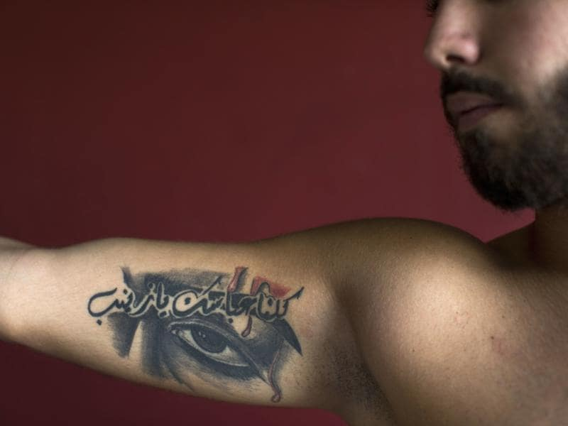 Abbas, 23, poses for a photo showing off his tattoos in Arabic that reads: We are all your Abbas, oh Zeinab. (AP)