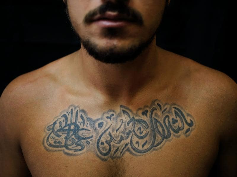 Alodi Issa, 22, poses for a photo showing off his tattoos. The tattoo in Arabic reads: Oh, the revenge for Hussein. Ali, Fatima. (AP)