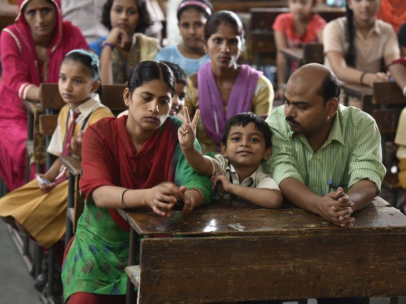 A boy sits in a classroom with his parents to meet teachers during the parent-teacher meeting at the Government Sarvodya Secondary School in Jorbagh, New Delhi. (Raj K Raj/HT PHOTO)