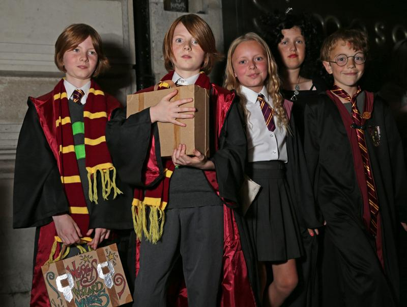 Children dressed as characters from Harry Potter books, pose for a photograph while waiting for their copy of the book in London.  (AFP)