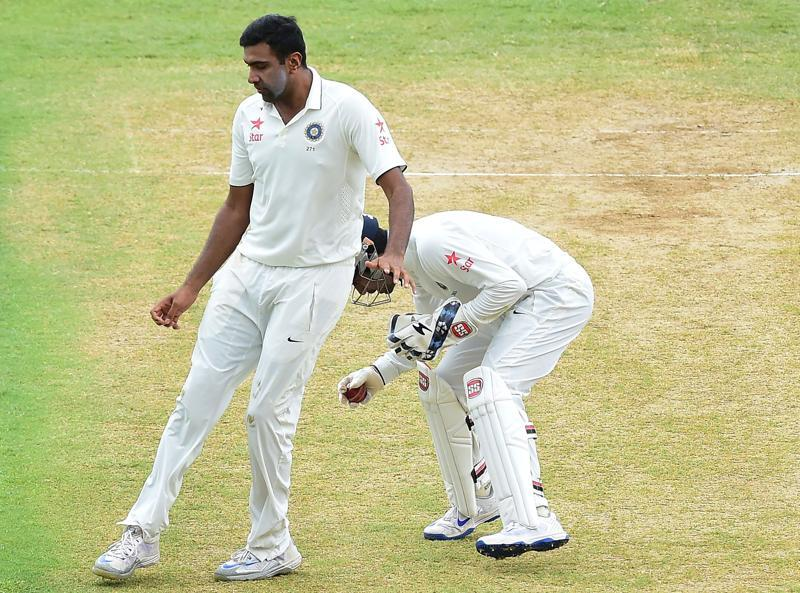 ACTION FIGURE: Ashwin was in the thick of action right through the day, even colliding with 'keeper Saha a little after scalping his fourth victim, Devendra Bishoo, in the  43rd over.  (AFP)