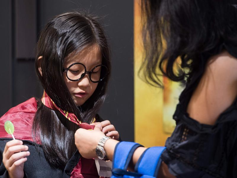 A mother  helping her daughter get dressed as a Harry Potter character in Hong Kong.  (AFP)