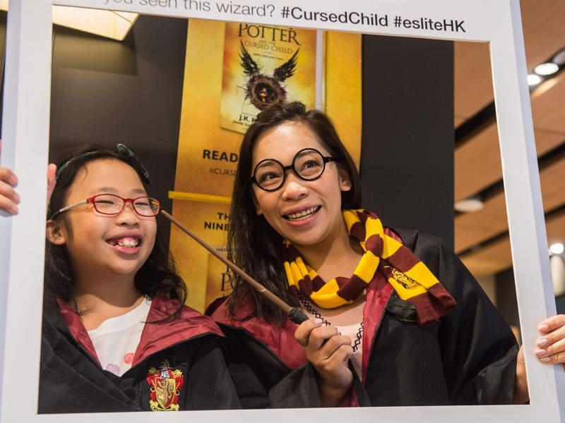 A mother and her daughter pose dressed up as Harry Potter characters in front of a poster at a bookstore in Hong Kong.  (AFP)