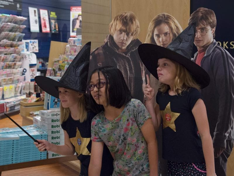 Potter fans pose for photographs against a poster at the launch of the book in Singapore on Sunday.  (AFP)