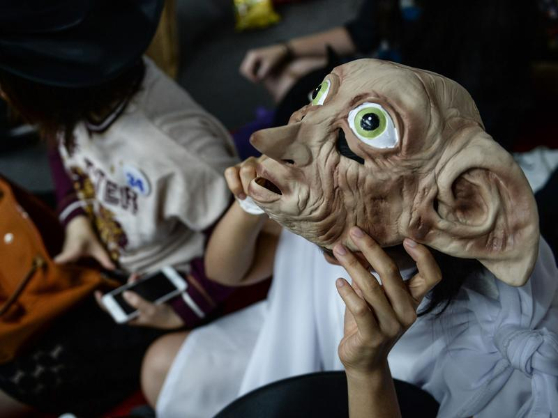 A Harry Potter fan dressed as Dobby waits to receive his copy of the book in Bangkok on Sunday.  (AFP)