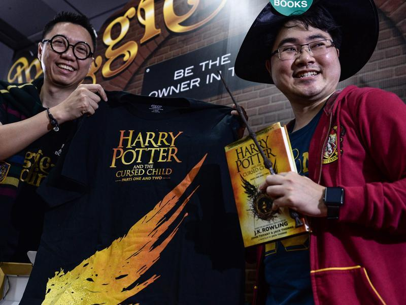 Potter fan Santipat Huangsawat (right) with the first of the new Harry Potter script book that was launched in Thailand on Sunday.  (AFP)