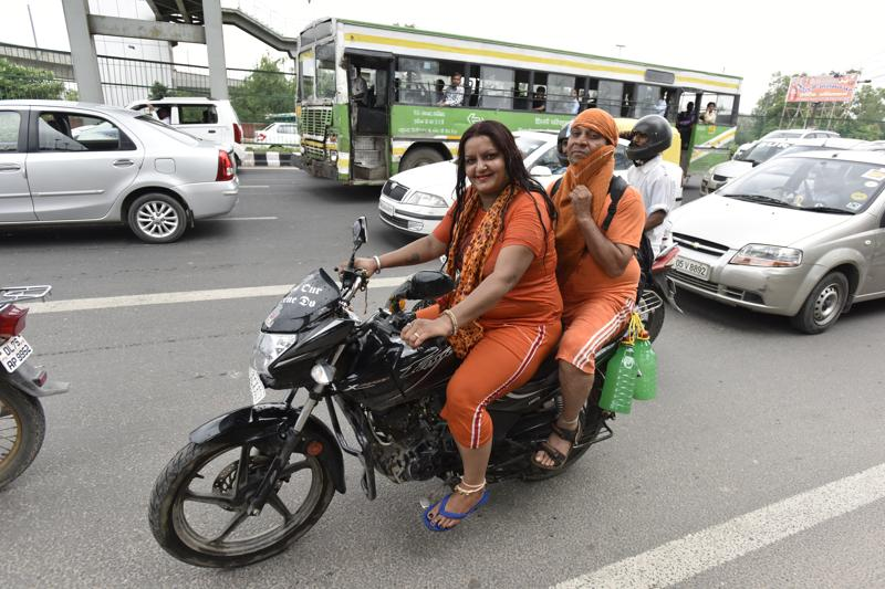 Kanwarias carrying holy water are seen on a bike at NH24 in New Delhi.  (Virendra Singh Gosain/HT PHOTO)