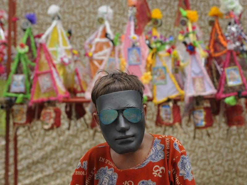 A Kanwaria wears a mask as he poses for a photograph at a resting camp, in Noida. (Burhaan Kinu/HT Photo)