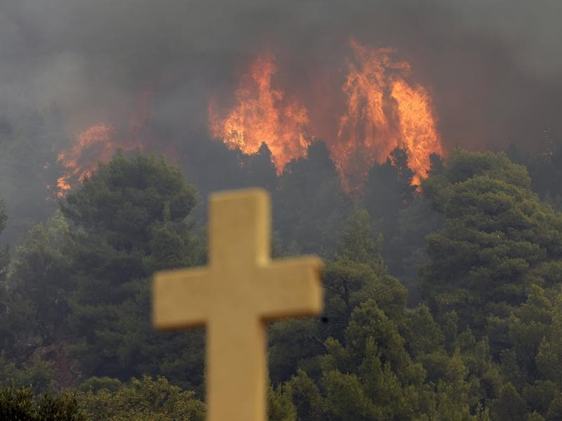Nearly 200 firemen, assisted by water-dropping aircraft, fire engines and volunteers, are fighting a large forest fire that has raged through the Greek island of Evia. (AP Photo)