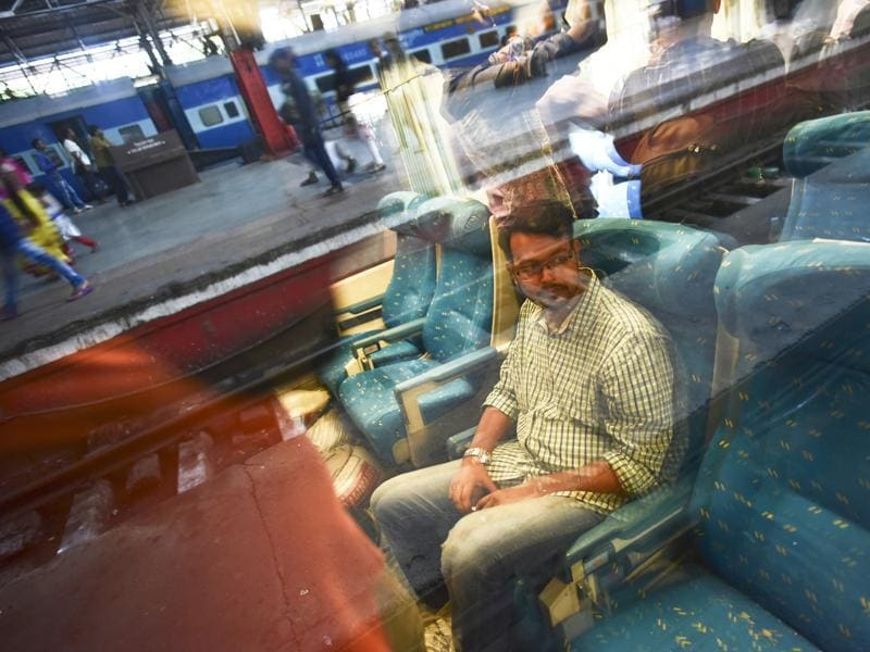 A Rail fan club member sits inside the coach, which have seats upholstered in blue.  The train traveled the distance in 12.5 hours at 130 km per hour speed during a trial run. (ARIJIT SEN/Hindustan Times)