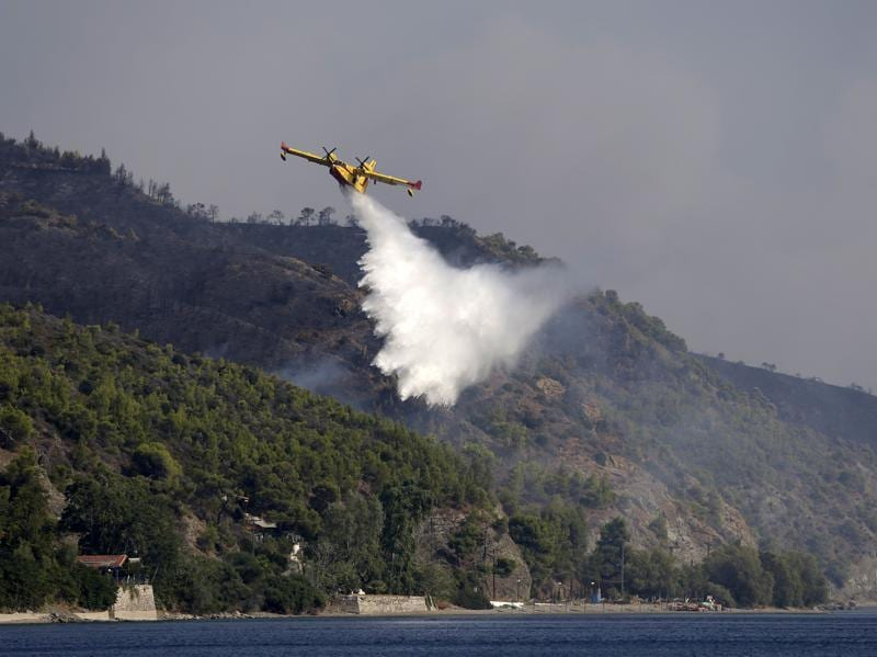 An aircraft drops water over a fire at the village of Limni on the island of Evia. (AP Photo)