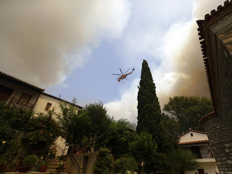 An helicopter operates over a fire next to Galataki Monastery near the seaside village of Limni. (AP Photo)