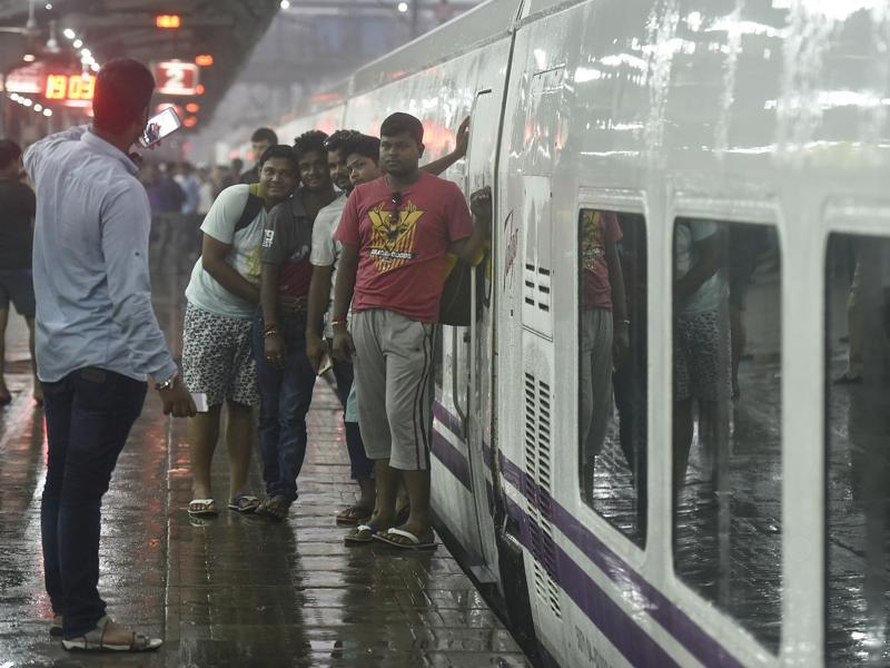 The train was delayed between Surat-Mumbai section as the tracks were washed away due to floods. But that did not stop onlookers from posing for pictures with the swanky white trains with purple stripes.     (Raj K Raj/HT PHOTO)