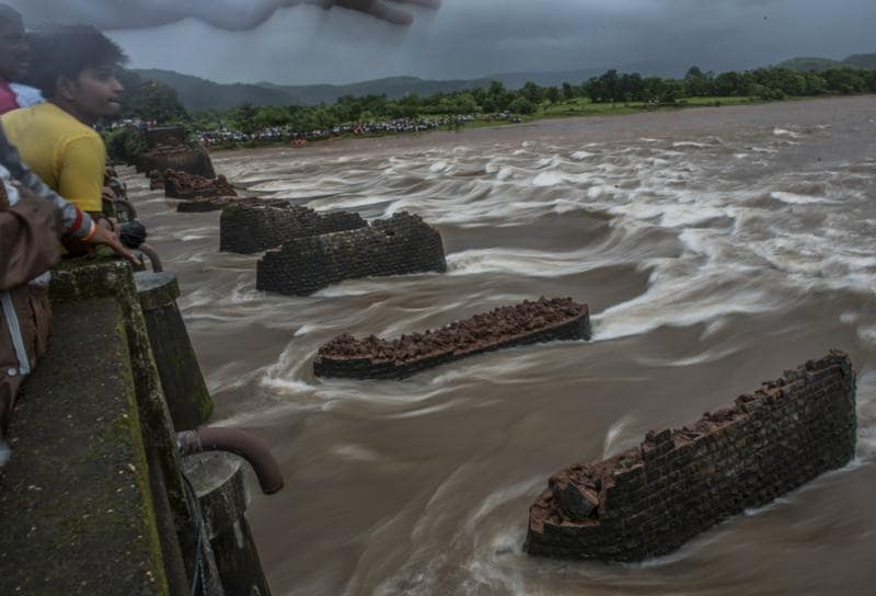 People watch as the search and rescue operation is going on after an old bridge connecting to the Mumbai-Goa highway collapsed and was washed away by the Savitri river late on Tuesday night in Mahad, India. (Satish Bate)
