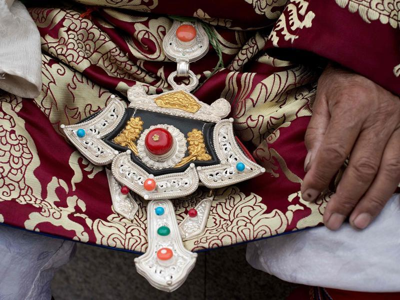 A Tibetan sports a silver waistband adorned with beads. (AFP)