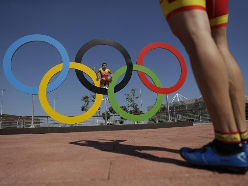 Spanish cyclist Tania Calvo poses for a picture for teammate Juan Peralta on the Olympics rings in the Olympic Park ahead of the 2016 Summer Olympics in Rio de Janeiro, Brazil. (AP Photo) (AP)