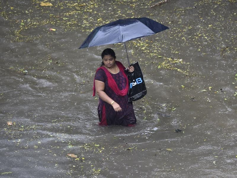 A Woman wades  through flooded water at sion during heavy rains in Mumbai on Friday. (Vijayanand Gupta)