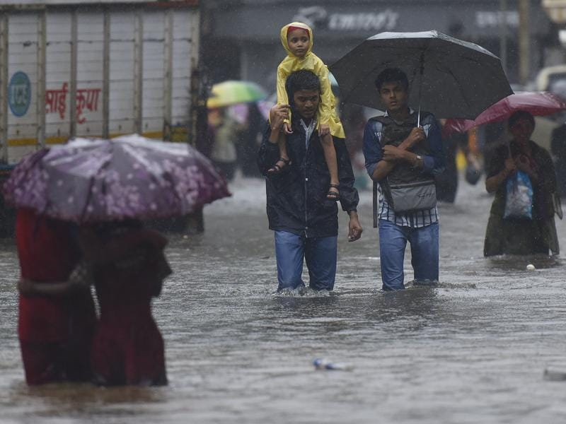 A man carries his child on his shoulder as they walk though the flooded water at sion during heavy rains in Mumbai. (Vijayanand Gupta)