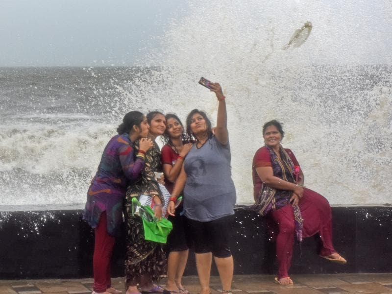 Mumbai, India - Aug. 5, 2016:People enjoy during a high tide at Worli seaface in Mumbai on Friday. (Pratik Chorge)