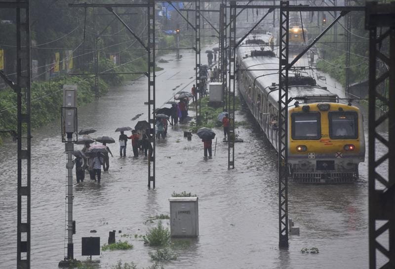 People wade through water logged  tracks as local trains stopped near Sion station after heavy rains in Mumbai on Friday. (Vijayanand Gupta/HT PHOTO)