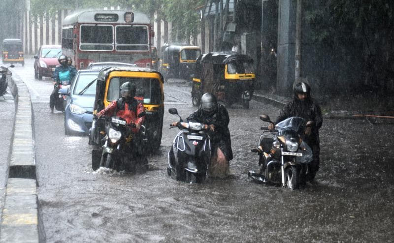 People dragging their bikes which stopped working due to water logging at Jogeshwari-Vikhroli Lilnk Road in Powai  on Friday. (Prashant Waydande)