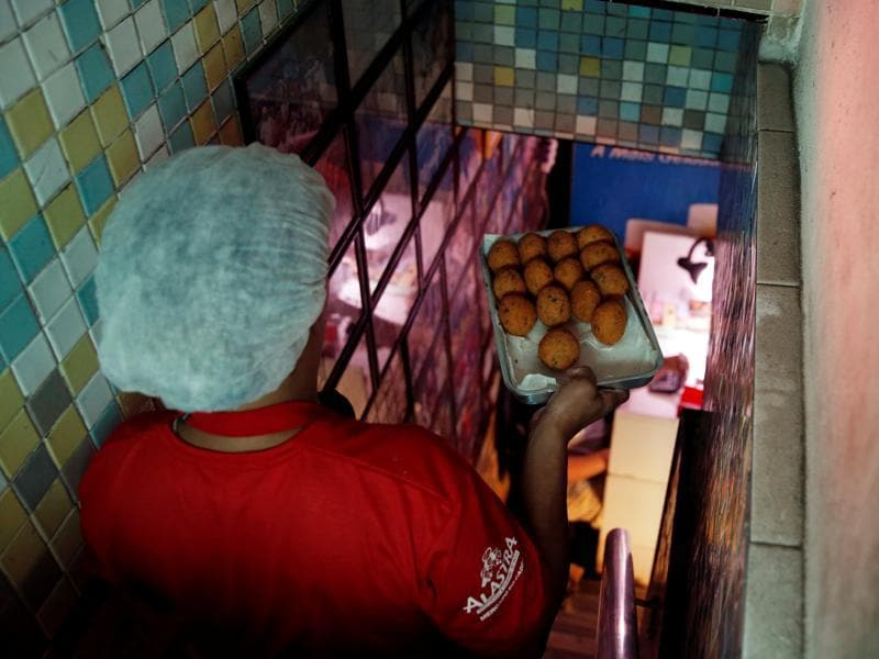 A woman prepares bolhinhos de bacalhau, or fried codfish balls, known to be the most famous Rio de Janeiro bar food. However, it's said that a really sublime bolhinho, with the right mix of salt-cod, flour, potatoes and spice fried in the right oil, is hard to find. (REUTERS)