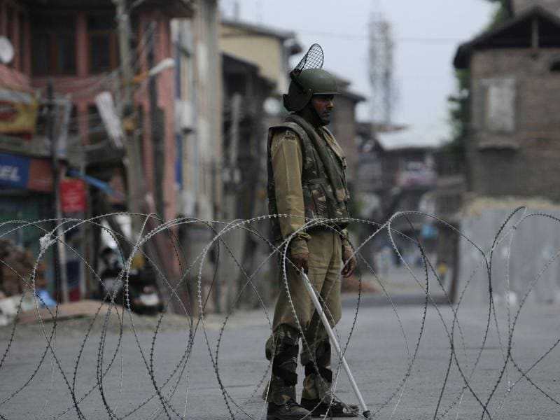 A paramilitary soldier stands guard near barbed wire set during a curfew in downtown Srinagar. (Waseem Andrabi /HT Photo)