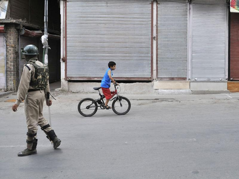 A Kashmiri boy rides a bicycle past a soldier in a deserted Srinagar street on July 19. (Waseem Andrabi /HT Photo)