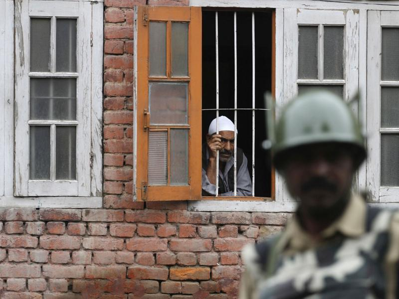 A Kashmiri man looks out from a window as a paramilitary soldiers stands guard during a curfew in Srinagar.  Kashmir has under rolling since the killing of Hizbul Mujahideen commander Burhan Wani in an encounter on July 8. Here are some snapshots from the past 30 days. (Waseem Andrabi /HT Photo)