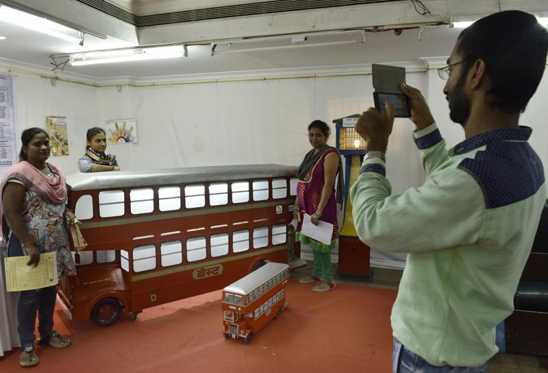 Visitors pose for a photograph next to a BEST bus model.  (ANSHUMAN POYREKAR)