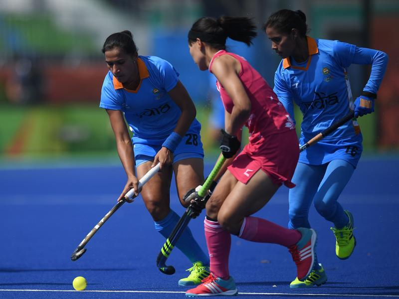 India's Rani (L) fights for the ball with Japan's Ayaka Nishimura (C) as India's Vandana Katariya looks on during the women's field hockey Japan vs India match. (AFP Photo)