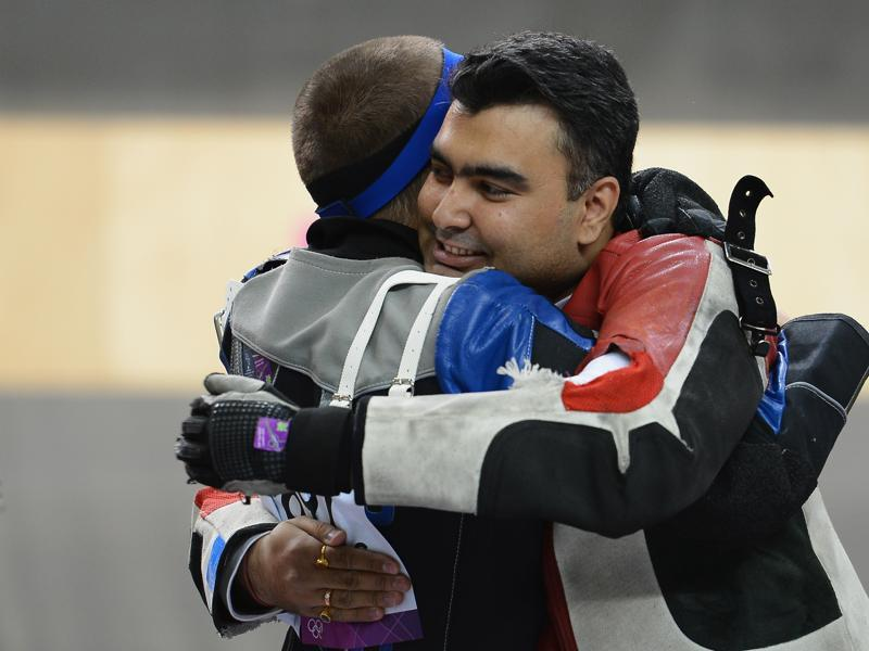 Alin George Moldoveanu of Romania, who won the gold, hugs Gagan Narang , who held onto to win the bronze at The Royal Artillery Barracks. Niccolo Campriani of Italy won silver that day. (Getty Images)