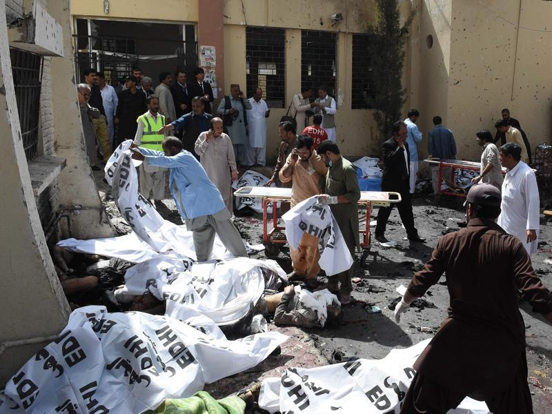 Pakistani volunteers cover the bodies of victims after the bomb explosion at a government hospital premises in Quetta (AFP)