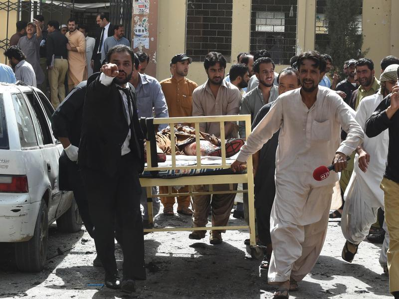 Pakistani lawyers and local media personnel carry a bed to move the body of a news cameraman after a bomb explosion at a government hospital premises in Quetta on Monday. (AFP)