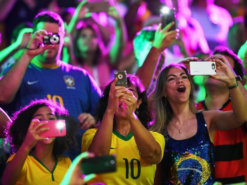 Supporters take pictures as they cheer for their team during the men's qualifying volleyball match between Brazil and Mexico at the Maracanazinho stadium. (AFP Photo)