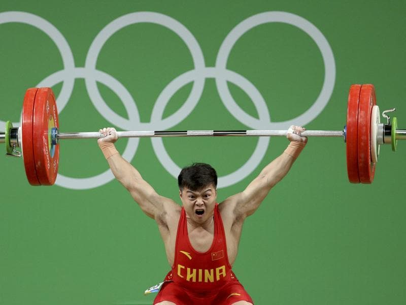Long Qingquan of China set a world record in winning Olympic gold in the men's weightlifting 53-kilogram category Sunday. (REUTERS)